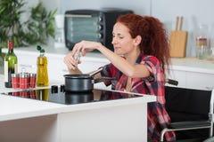 Matlagning för rörelsehindrad kvinna i kök royaltyfri fotografi