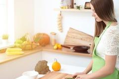 Matlagning för ung kvinna i köket Hemmafru som skivar ny sallad royaltyfri fotografi