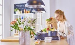 Matlagning f?r ung kvinna i k?ket sund mat arkivbilder