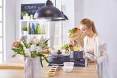 Matlagning f?r ung kvinna i k?ket sund mat royaltyfri foto