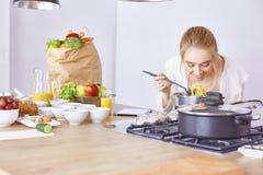 Matlagning f?r ung kvinna i k?ket sund mat fotografering för bildbyråer