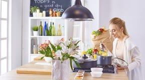 Matlagning f?r ung kvinna i k?ket sund mat arkivfoto