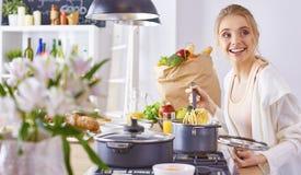 Matlagning f?r ung kvinna i k?ket sund mat arkivbild