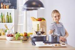 Matlagning f?r ung kvinna i k?ket sund mat royaltyfri fotografi