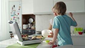 Matlagning f?r ung kvinna svamlar i k?k, och den gulliga pojken hj?lper henne E stock video