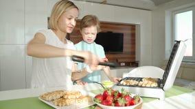 Matlagning f?r ung kvinna svamlar i k?k, och den gulliga pojken hj?lper henne E lager videofilmer