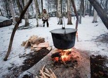 Matlagning i en kruka på branden arkivfoton