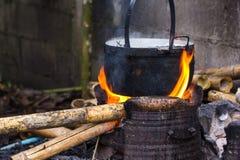 Matlagning i kitteln som slickas av flammor på öppen brand fi royaltyfri foto