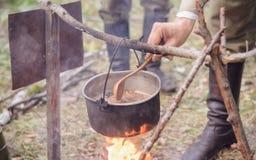 Matlagning i kruka på branden arkivbild