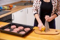 Matlagning, mat och hem- begrepp - som är nära av kvinnlig, räcker upp gnisslande ost royaltyfri foto