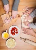 Matlagning med barn Barn- och moderhänder knådar och rullar dou arkivfoto