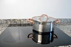 Matlagning med induktionsspisen arkivbild