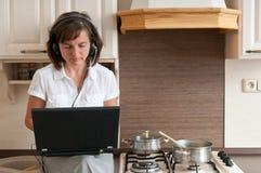 Matlagning och arbete hemifrån arkivbild