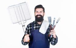 Matlagning- och matportion Lyckligt hipsterinnehavraster och rostfritt stålmatlagningredskap Skäggig man med spisgallret och arkivbild