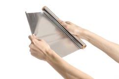 Matlagning- och shishaämne: mänsklig hand som rymmer en folie isolerad på vit bakgrund i studio royaltyfria foton
