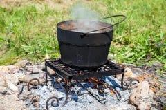Matlagning på en lägerbrand utomhus i sommardag arkivfoto