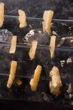 Matlagning på naturen Stekhet smaklig bacon på fyrpannan med brasan och kol Royaltyfri Fotografi