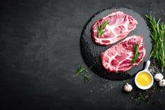 Matlagning på nytt rått griskött för köksbordet marmorerade biffar på svart bakgrund arkivfoton