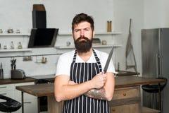 Matlagning ?r min passion brutal man i kockförkläde med den skarpa kniven mogen man med att laga mat f?r sk?gg Kulinarisk aff?r royaltyfria bilder