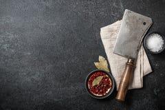 Matlagningbakgrund med tappningslaktareköttyxan och kryddor på bl royaltyfria bilder