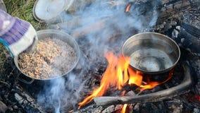 Matlagningbovetehavregröt och värmevatten på öppen brand arkivfilmer