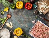 Matlagningförberedelse av Klocka färgrika paprikapeppar och köttfärs med ris på det lantliga köksbordet Arkivfoto