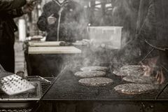 Matlagninghamburgare på en nattstadsgata royaltyfria bilder