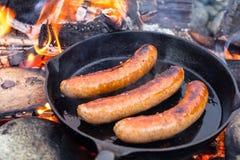 Matlagningkorvar i gjutjärnkastrull på lägereld, medan campa Bra och positiv lägereldmat Royaltyfria Foton