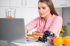 Matlagningkvinna som ser bärbara datorn, medan förbereda mat i kök Royaltyfri Foto