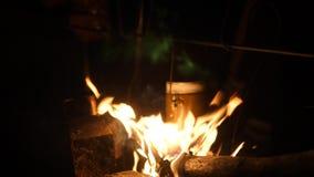Matlagningmål i en kokkärl på brinnande lägereld i löst campa på nattnattlägereld lopp som fotvandrar att campa för affärsföretag arkivfilmer