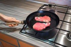Matlagningnötköttbiffar som grillar i en gjutjärnstekpanna Arkivbilder