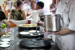 Matlagningpannkakor, stekheta pannkakor, rostade pannkakor, kock som förbereder mat Royaltyfri Fotografi