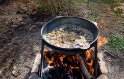 Matlagningpilaff i en stor kittel på en öppen brand utomhus på en solig sommardag Horisontalramen royaltyfri fotografi