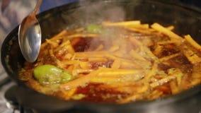 Matlagningpilaff, shef tar bort vitlök och gräsplanchilipeppar från den järn- kokkärlet lager videofilmer