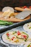 Matlagningprocess av mini- pizza för danande - som är liten och som är personlig, med ost, tomater och sparris Royaltyfri Bild