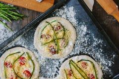 Matlagningprocess av mini- pizza för danande - som är liten och som är personlig, med ost, tomater och sparris Arkivfoton