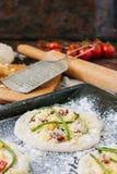 Matlagningprocess av mini- pizza för danande - som är liten och som är personlig, med ost, tomater och sparris Royaltyfri Foto