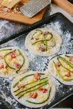 Matlagningprocess av mini- pizza för danande - som är liten och som är personlig, med ost, tomater och sparris Royaltyfri Fotografi