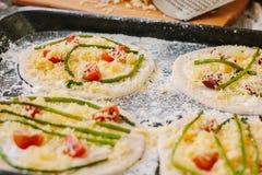 Matlagningprocess av mini- pizza för danande - som är liten och som är personlig, med ost, tomater och sparris Royaltyfria Bilder