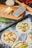 Matlagningprocess av mini- pizza för danande - som är liten och som är personlig, med ost, tomater och sparris Royaltyfria Foton