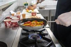 Matlagningprocess i en panna arkivfoto