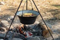 Matlagningsoppa i en kokkärl på en öppen brand Arkivfoton