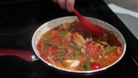 Matlagningtomater, höna och sparris i en panna lager videofilmer
