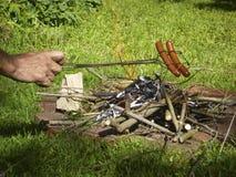 Matlagningvarmkorvar över lägerelden Royaltyfri Fotografi