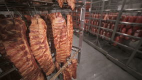 Matlagring, lager Köttprodukter korvar som hänger på kuggar i ett köttlager, frys arkivfilmer