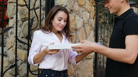 Matleverans Kurir Giving Woman Box med pizzadet fria arkivfilmer