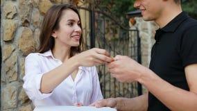 Matleverans Kurir Giving Woman Box med pizzadet fria lager videofilmer