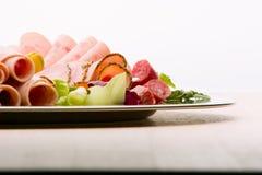Matmagasin med läcker salami, stycken av skivad skinka, korven, tomater, sallad och grönsaken - royaltyfri foto