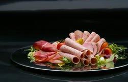 Matmagasin med läcker salami, stycken av skivad skinka, korven, tomater, sallad och grönsaken - arkivbild