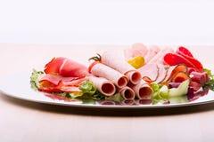 Matmagasin med läcker salami, stycken av skivad skinka, korven, tomater, sallad och grönsaken - royaltyfri fotografi